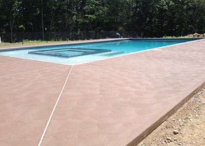 Tan swirl finished concrete decking for swimming pools